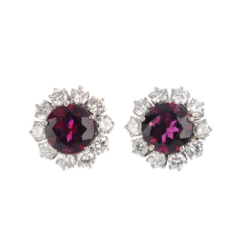 474 - A pair of tourmaline and diamond cluster earrings. Each designed as a circular-shape purplish red to...