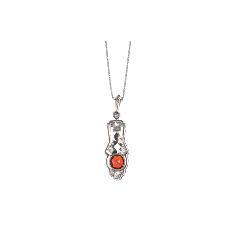 475 - A garnet and diamond pendant. The oval-shape garnet collet, with vari-cut diamond surround and openw...