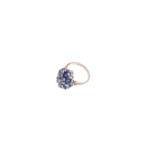 480 - A mid 20th century sapphire and diamond cluster ring. The oval-shape sapphire, with similarly-cut sa...