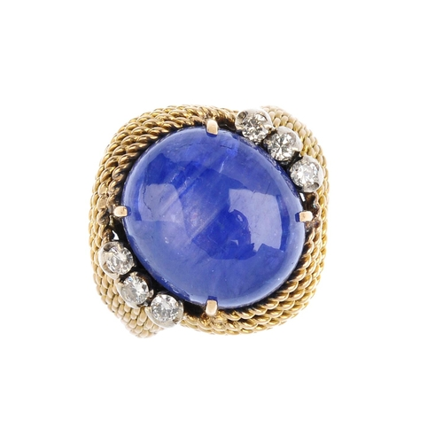 485 - A Ceylon sapphire and diamond dress ring. The oval star sapphire cabochon, with brilliant-cut diamon...