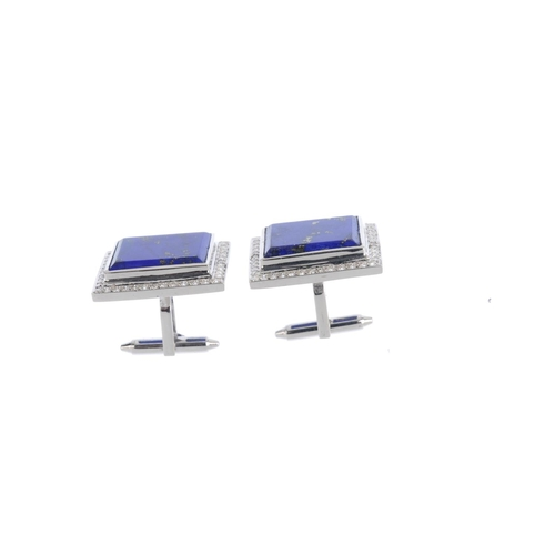 486 - A pair of lapis lazuli and diamond cufflinks. Each designed as a rectangular-shape lapis lazuli pane...