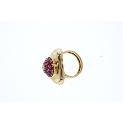498 - A diamond and ruby dress ring. The pave-set ruby dome, with central brilliant-cut diamond highlight,...