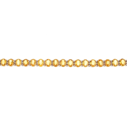 5 - A sapphire and diamond bracelet. Designed as a series of oval-shape yellow sapphires, with brilliant...