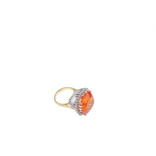 504 - An 18ct gold fire opal and diamond cluster ring. The cushion-shape fire opal, raised within a brilli...