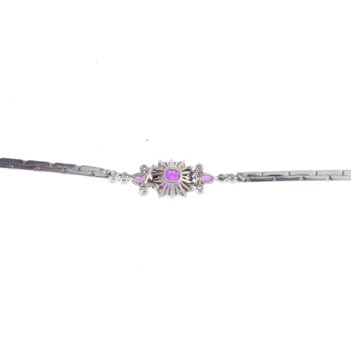 55 - A ruby and diamond bracelet. The oval-shape ruby and brilliant-cut diamond cluster, with marquise-sh...