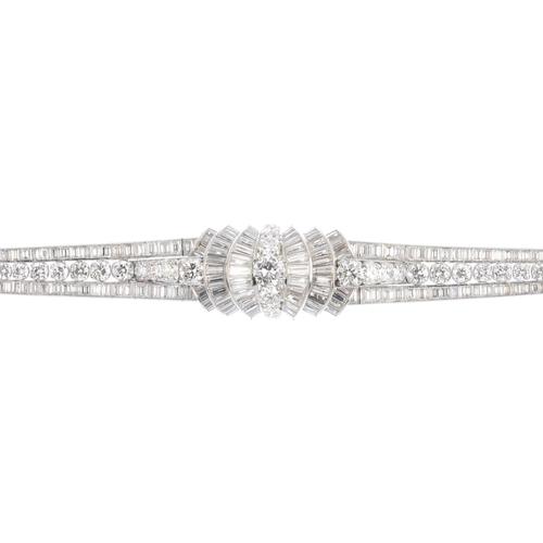 58 - A mid 20th century diamond bracelet. The graduated brilliant-cut diamond line, with baguette-cut dia...