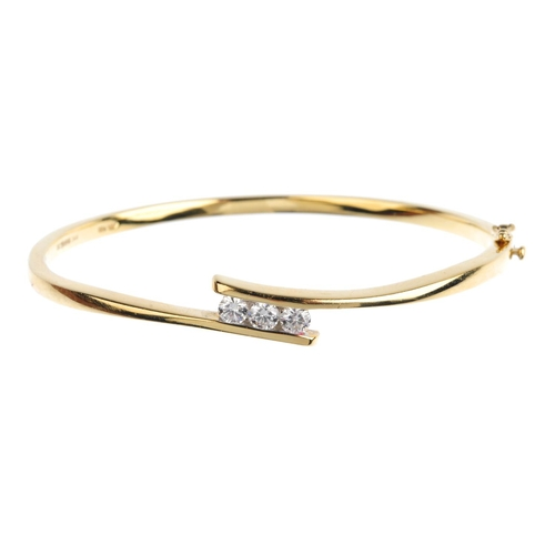 6 - An 18ct gold diamond hinged bangle. The brilliant-cut diamond line, with crossover sides. Estimated ...