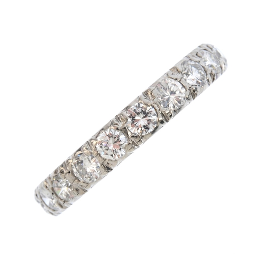 60 - A mid 20th century platinum diamond full eternity ring. The brilliant-cut diamond line, with scrolli...