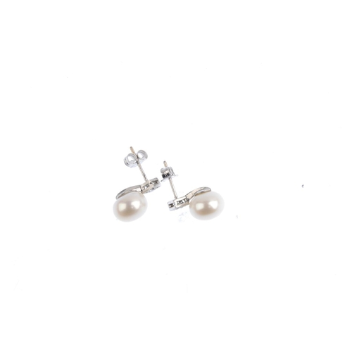 65 - A pair of cultured pearl and diamond earrings. Each designed as a cultured pearl, measuring 9.6mms, ...