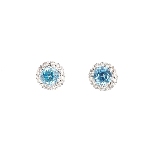 69 - A pair of zircon and diamond earrings. Each designed as a circular-shape blue zircon, with single-cu...
