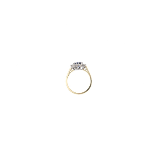 71 - An 18ct gold sapphire and diamond cluster ring. The circular-shape sapphire, with brilliant-cut diam...