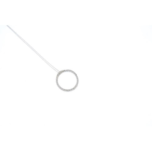73 - A diamond pendant. Designed as a brilliant-cut diamond circle, suspended from a trace-link chain. Es...