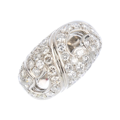 77 - BULGARI - a diamond dress ring. Comprising two pave-set diamond asymmetric scrolling panels, with un...