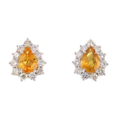 8 - A pair of sapphire and diamond cluster earrings. Each designed as a pear-shape yellow sapphire, with...