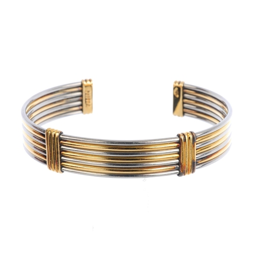 87 - CARTIER - an 'Ariana' bangle. The bi-colour cuff, comprising a series of seven curved bars, with gro...