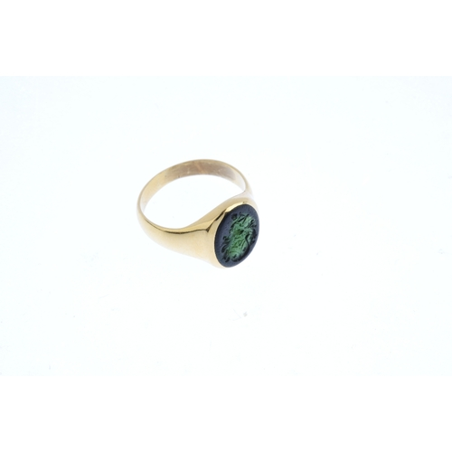363 - A mid 20th century gold tourmaline signet ring. The oval-shape green tourmaline intaglio, carved wit...