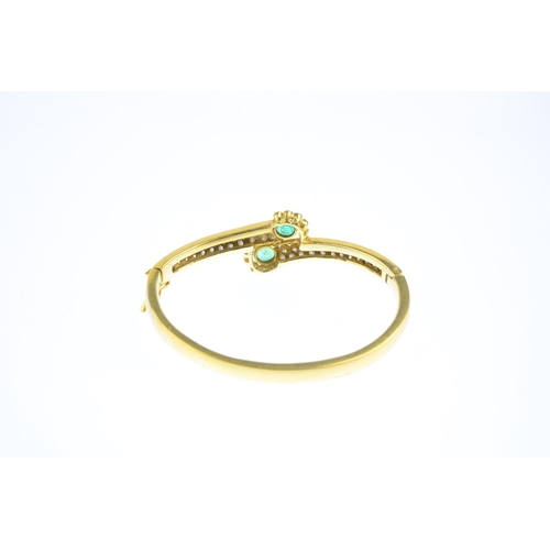 100 - An emerald and diamond hinged bangle. Of crossover design, the circular-shape emerald and brilliant-...