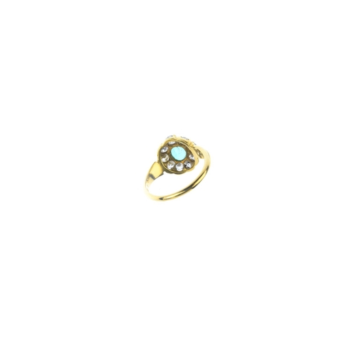 107 - An emerald and diamond cluster ring. The oval-shape emerald, with old-cut diamond surround and styli...