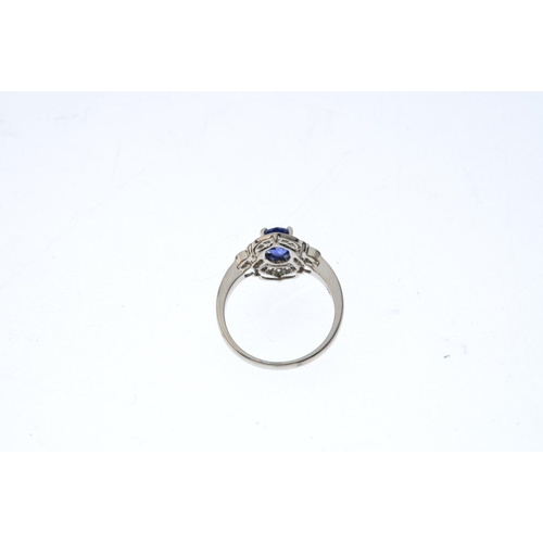 110 - A sapphire and diamond cluster ring. The oval-shape sapphire, with brilliant-cut diamond trefoil and...