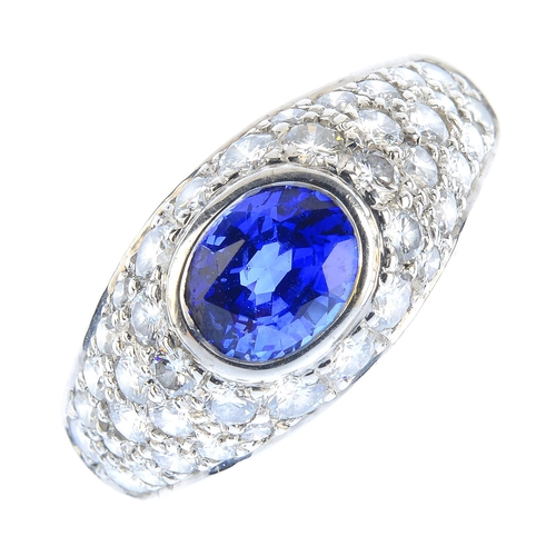 111 - A Ceylon sapphire and diamond dress ring. The oval-shape sapphire collet, with pave-set diamond surr...