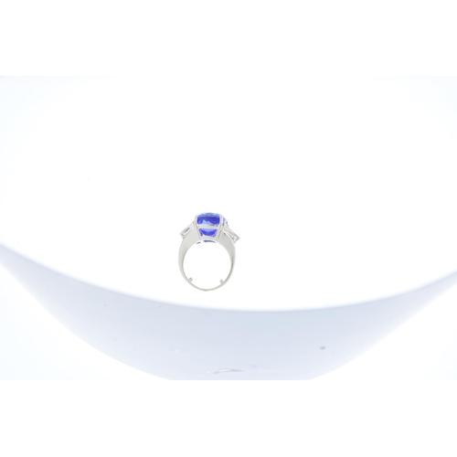 112 - An 18ct gold tanzanite and diamond three-stone ring. The cushion-shape tanzanite, with triangular-sh...