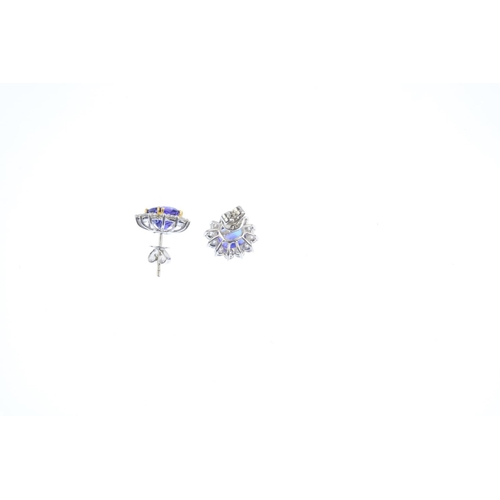 113 - A pair of tanzanite and diamond earrings. Each designed as a cushion-shape tanzanite, with brilliant...