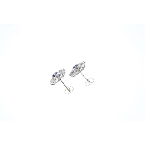 117 - A pair of sapphire and diamond cluster earrings. Each designed as a circular-shape sapphire, with ol...