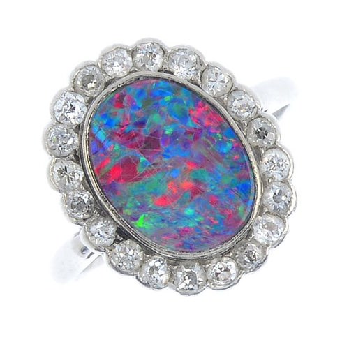12 - An early 20th century platinum, opal doublet and diamond cluster ring. The oval opal doublet, with c...
