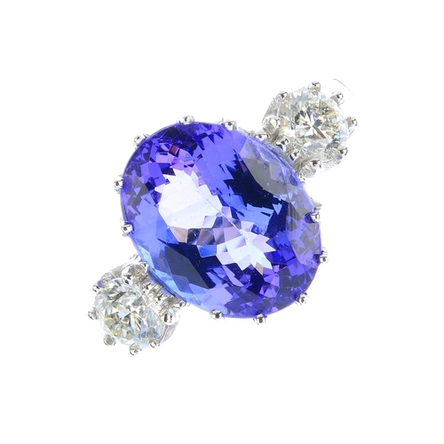 121 - A tanzanite and diamond ring. The oval-shape tanzanite, with brilliant-cut diamond sides and grooved...