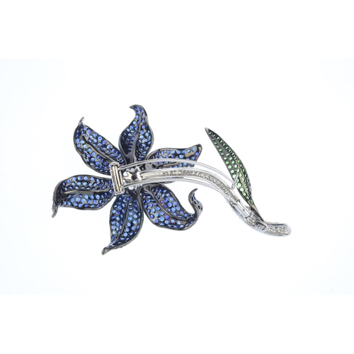 124 - A diamond, sapphire and tsavorite garnet floral brooch. The graduated brilliant-cut diamond stamens,...