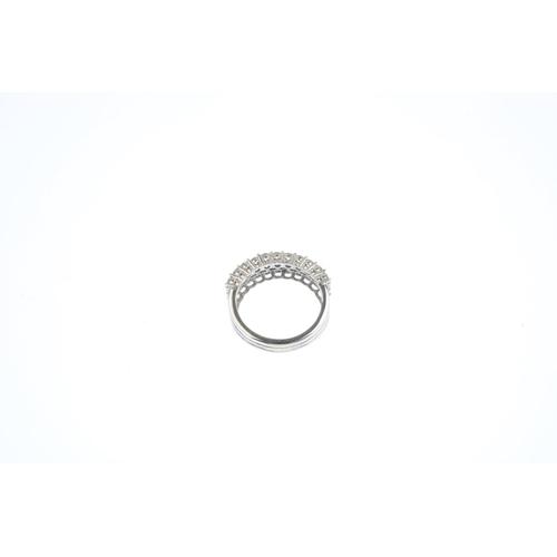 129 - An 18ct gold diamond half eternity ring. Designed as three brilliant-cut diamond lines, with openwor...
