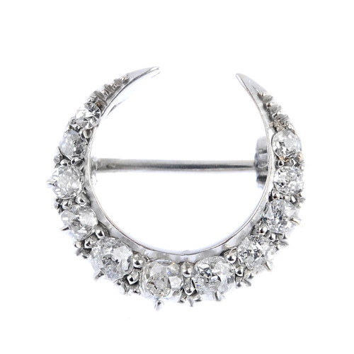 13 - An early 20th century gold diamond crescent brooch. Designed as a graduated old-cut diamond line. Es...