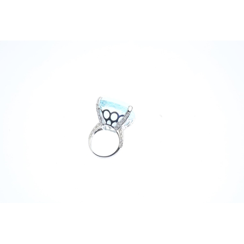 132 - An aquamarine and diamond dress ring. The cushion-shape aquamarine, with openwork gallery, pave-set ...