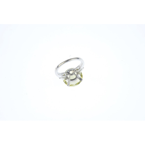 133 - A chrysoberyl single-stone and diamond ring. The circular-shape chrysoberyl, with tapered baguette-c...