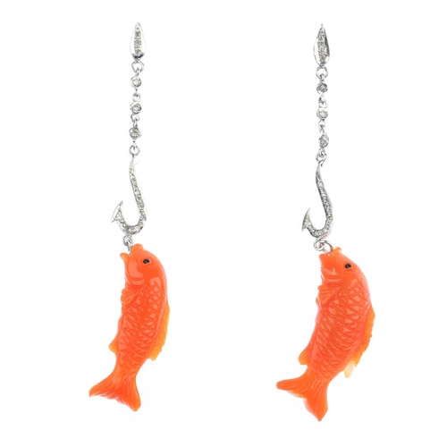 135 - A pair of coral and diamond earrings. Each designed as a carved coral fish, suspended from a single-...