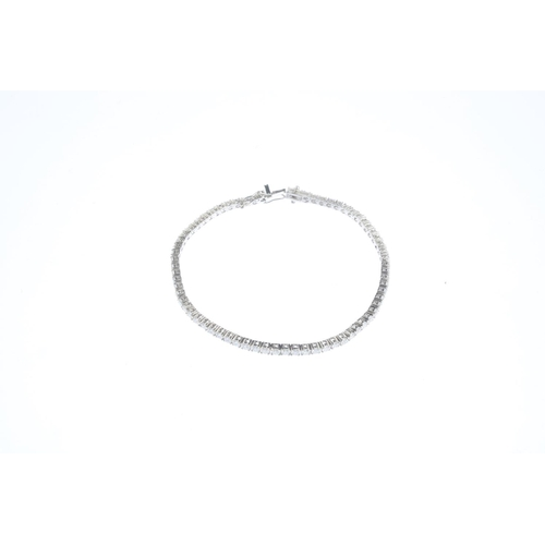 144 - An 18ct gold diamond bracelet. The brilliant-cut diamond line, with partially-concealed push-piece c...