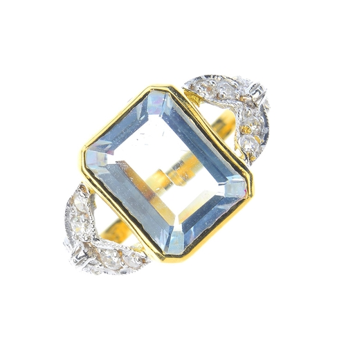 145 - An aquamarine and diamond dress ring. The rectangular-shape aquamarine, with vari-cut diamond foliat...