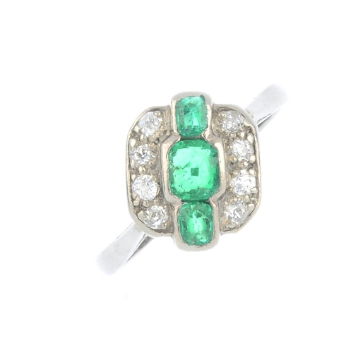 159 - An Art Deco gold and platinum emerald and diamond ring. Of geometric design, the graduated cushion-s...
