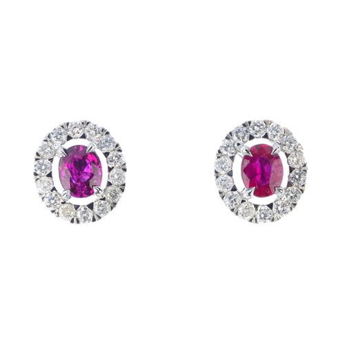 16 - A pair of ruby and diamond cluster earrings. Each designed as an oval-shape ruby, within a brilliant...