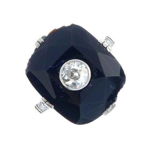 160 - An Art Deco 18ct gold onyx and diamond ring. The old-cut diamond collet, set within a faceted, curve...