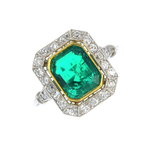 167 - A Colombian emerald and diamond cluster ring. The rectangular-shape emerald, with old-cut diamond ha...