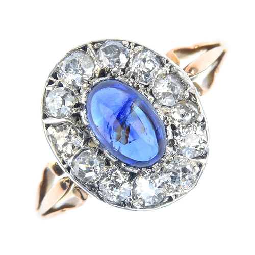 183 - A sapphire and diamond cluster ring. The oval sapphire cabochon, weighing 1.18cts, with old-cut diam...