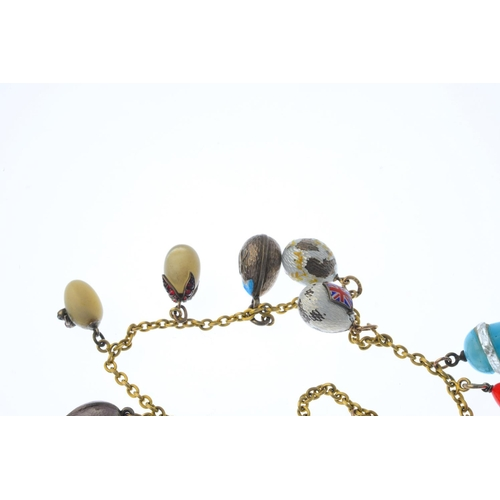 186 - A Russian pre-revolutionary egg charm bracelet. The gold grooved trace-link chain, with hook clasps,...