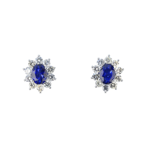 19 - A pair of sapphire and diamond cluster earrings. Each designed as an oval-shape sapphire, with brill...