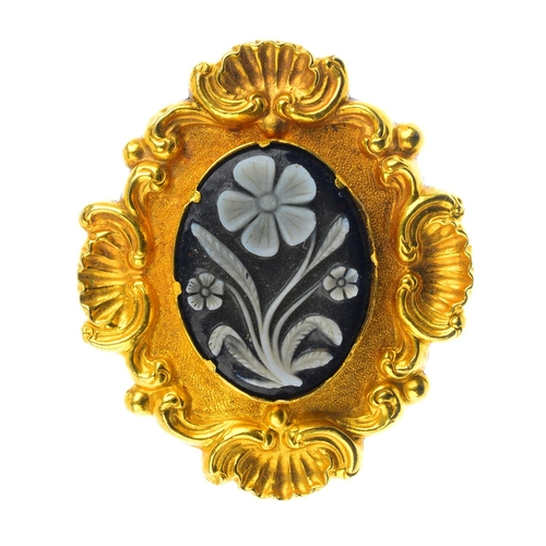 198 - A mid Victorian gold onyx cameo mourning brooch. The oval cameo panel, depicting a forget-me-not, wi...