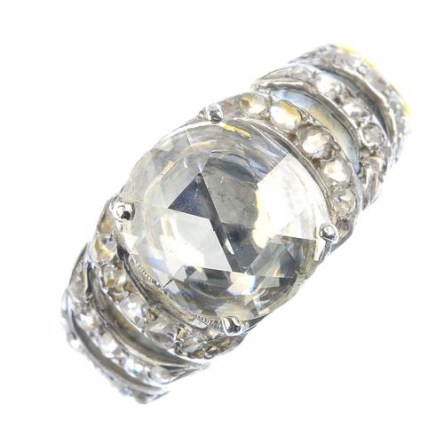 205 - A diamond single-stone ring. The oval-shape rose-cut diamond, with similarly-cut diamond curved open...
