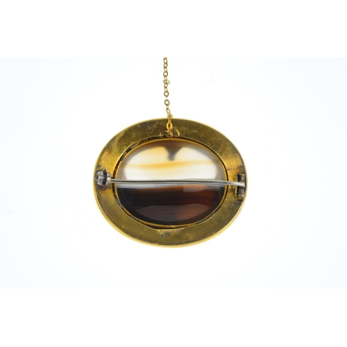 206 - A mid Victorian 18ct gold banded agate brooch. The oval banded agate cabochon, enclosed within a bea...