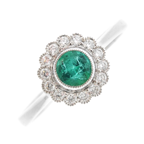 209 - An 18ct gold emerald and diamond cluster ring. The circular-shape emerald, with brilliant-cut diamon...