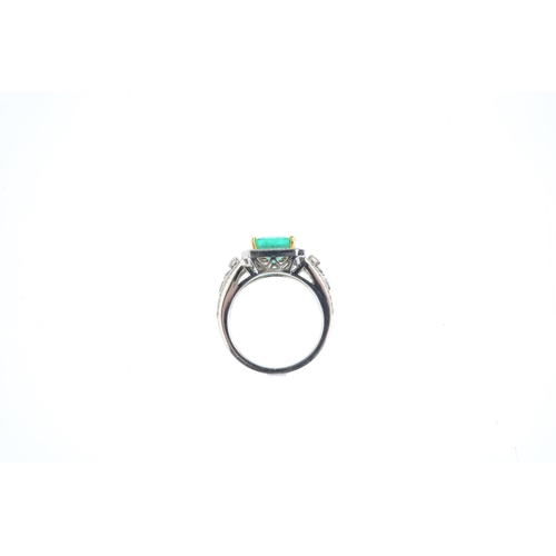 211 - An emerald and diamond cluster ring. The square-shape emerald, with brilliant-cut diamond surround a...