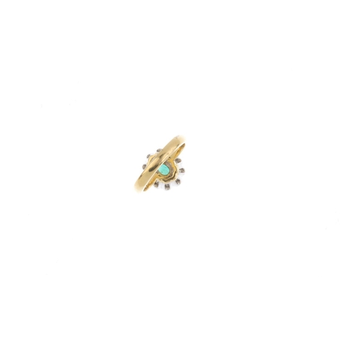 24 - An 18ct gold emerald and diamond cluster ring. The oval-shape emerald, within a brilliant-cut diamon...